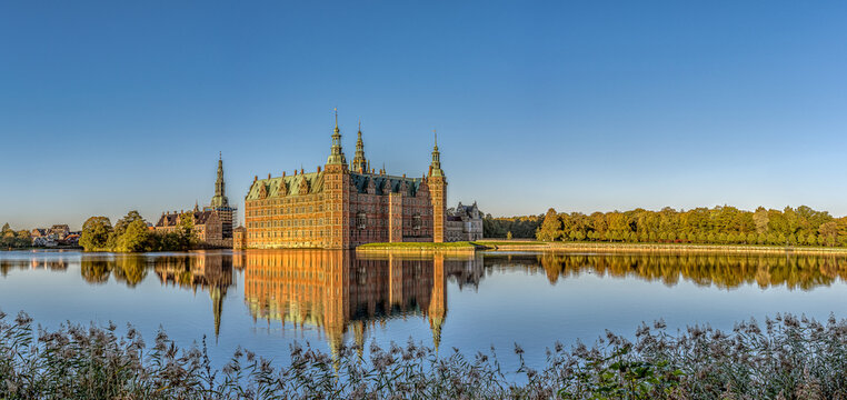 Panoramic view of Frederiksborg Castle in a mirror-gloss reflection at surise