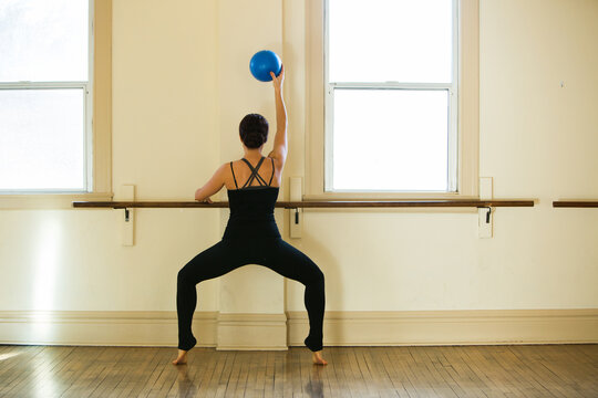 Woman doing exercise with ballet barre and exercise ball in dance studio. One arm raised holding blue ball.