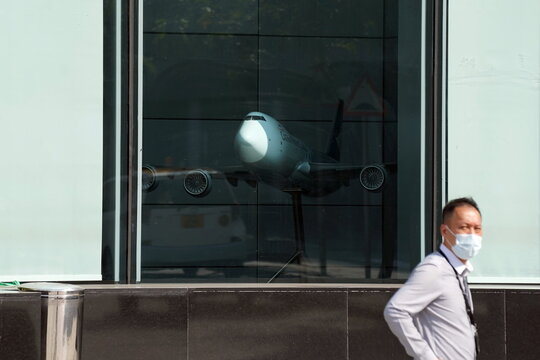 Man stands near an airplane model at Cathay City, the headquarters of Cathay Pacific, in Hong Kong