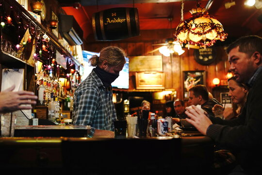 A bartender wearing a facial covering works while people drink and socialize as the coronavirus disease (COVID-19) outbreak continues in Milwaukee