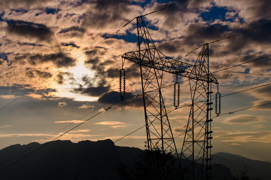 Current pylon in silhouette at sunset in the hills