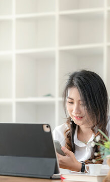 Young asian woman using smartphone while sitting at her office desk. Vertical view.