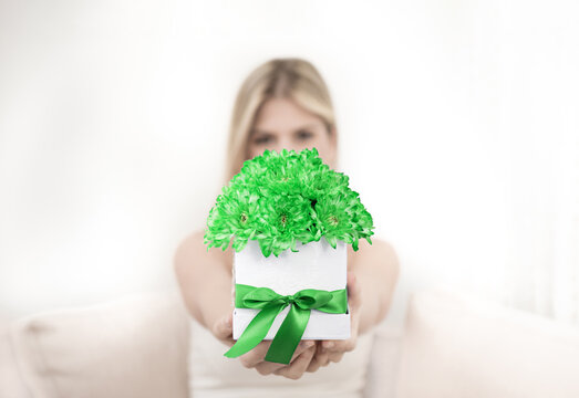A young blonde is holding a bouquet of green chrysanthemum flowers in a decorative box. The focus is on flowers.