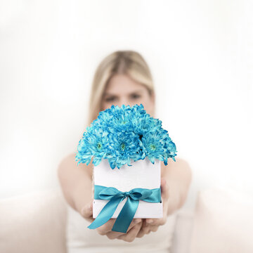 A young blonde is holding a bouquet of turquoise chrysanthemum flowers in a decorative box. The focus is on flowers.
