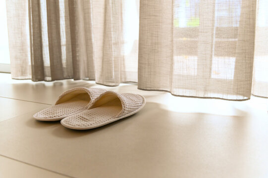 White slippers by white sheer curtains and soft sunlight, vacation concept.