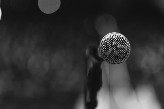 Close up of microphone over abstract blurred of attendee in seminar room or conference hall