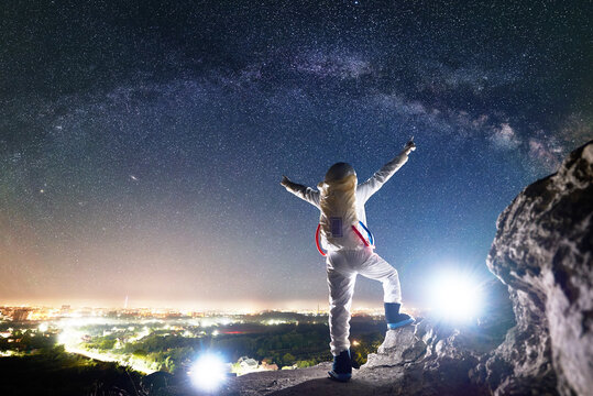 Back view of space traveler spreading arms out to sides while standing on rocky hill under beautiful sky with stars. Mission specialist astronaut in space suit enjoying view of milky way, night city