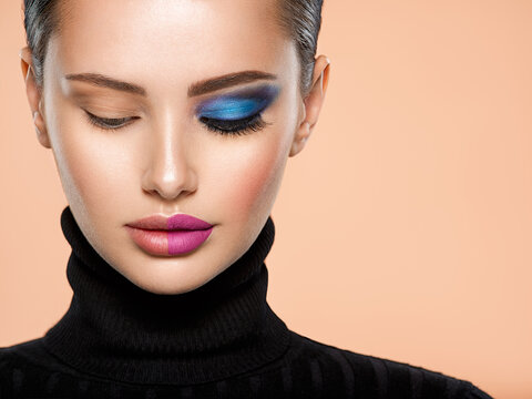 One half face of a beautiful white woman with  bright makeup and the other is natural. Woman portrait with a deep blue eye makeup of one eye. Natural and  vivid make-up on a female face. Fashion style