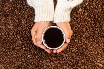 Manos de mujer sosteniendo una taza de café negro sobre un fondo de granos de café. Vista superior y de cerca