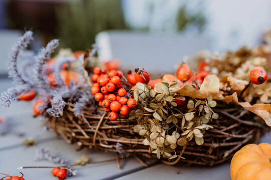 Close up photo of floral autumn door wreath made from natural materials: colorful rosehip berries, rowan, dry flowers and plants. Fall flower decoration. Florist workplace.