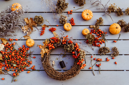 Making floral autumn door wreath from natural materials: colorful rosehip berries, rowan, dry flowers and pumpkins. Fall flower decoration workshop. Top view.