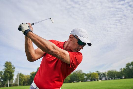 Male golfer doing a golf swing outdoors