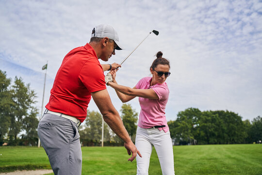 Golfer mastering a swing technique assisted by her coach