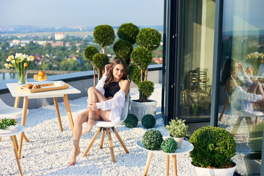 Happy female in white shirt with bare legs is enjoying sunshine at breakfast on terrace overlooking lake and city in the distance under sunny rays. On table is vase of flowers, coffee and croissants