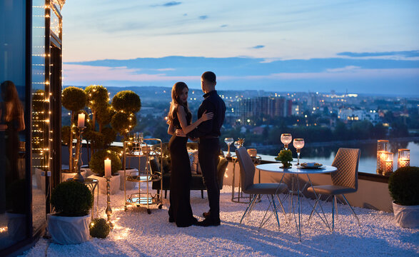 Attractive young woman and man having romantic date at rooftop restaurant. Lady in elegant dress touching boyfriend arm while he holding her waist and enjoying city view. Concept of love and romance.