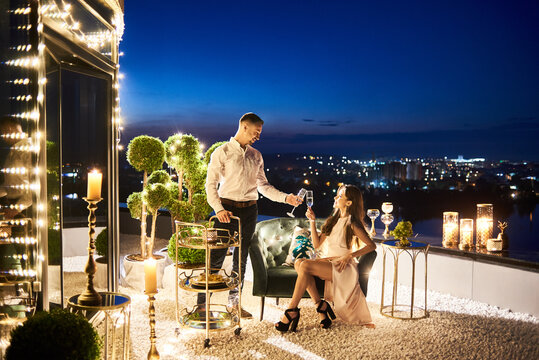 Side view of beautiful couple in love toasting with champagne at rooftop restaurant with magnificent night cityscape on background. Lady in evening dress and elegant gentleman having romantic date.