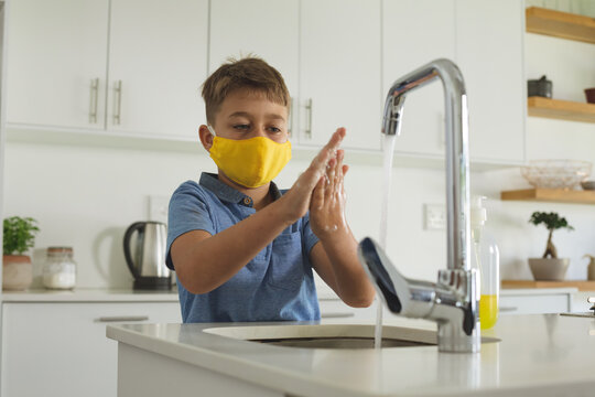 Boy wearing face mask washing his hands in the sink