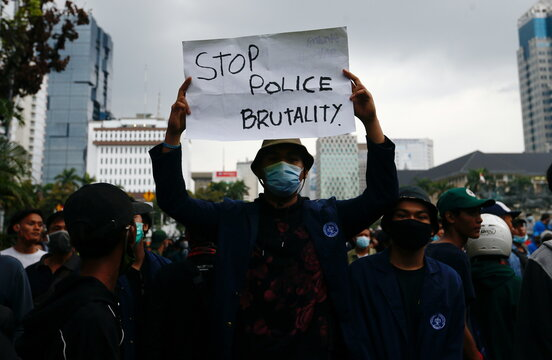 """A university student holds sign reading """"stop police brutality"""" during protest against the government's labor reforms bill"""