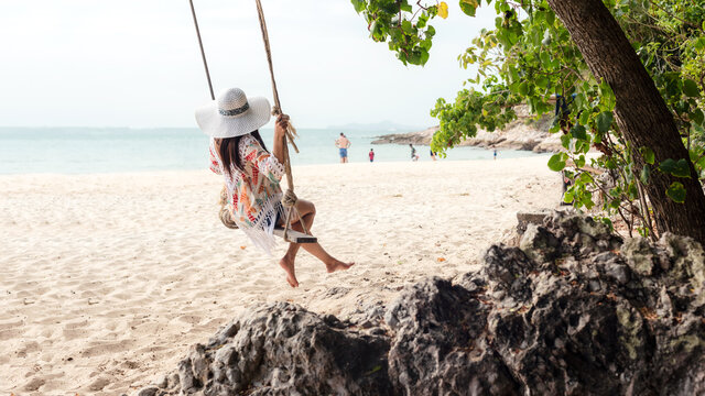 Summer Vacations. Lifestyle women relaxing and enjoying swing on the sand beach, fashion stunning young people on the tropical island so happy and luxury in holiday summer.