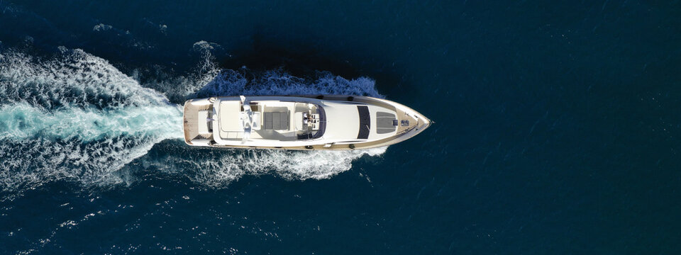 Aerial drone ultra wide photo of luxury yacht with wooden deck cruising in Aegean deep blue sea