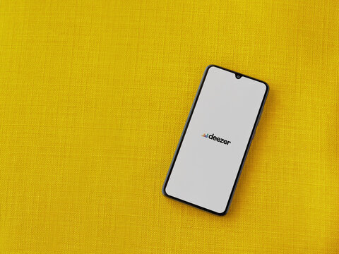 Lod, Israel - July 8, 2020: Deezer Music Player app launch screen with logo on the display of a black mobile smartphone on a yellow fabric background. Top view flat lay with copy space.