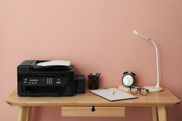 New modern printer and office supplies on wooden table