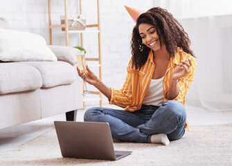 Black woman drinking wine during virtual party