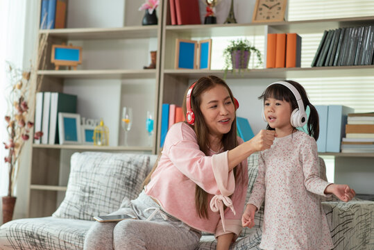 Asian child having fun and dancing with her mother in a room, active leisure and lifestyle concept