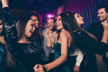 Photo of young people dancing in night club with neon lights chilling together laughing enjoying...