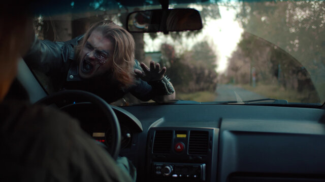 Zombie man attacking woman driving car on empty road