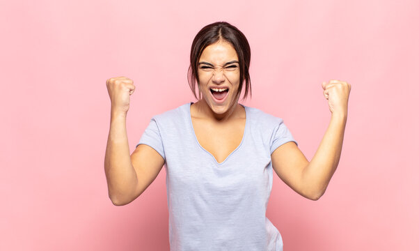 pretty young woman shouting aggressively with an angry expression or with fists clenched celebrating success