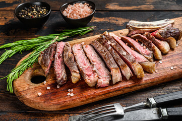 Ribeye steak on the bone. Grilled Beef meat. Wooden dark background. Top view