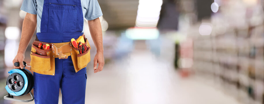 Closeup view of electrician with tools at store, space for text. Banner design