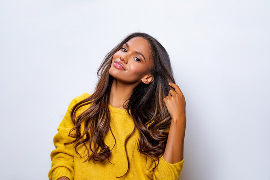 Portrait of beautiful black woman in yellow sweater with long curly hair.