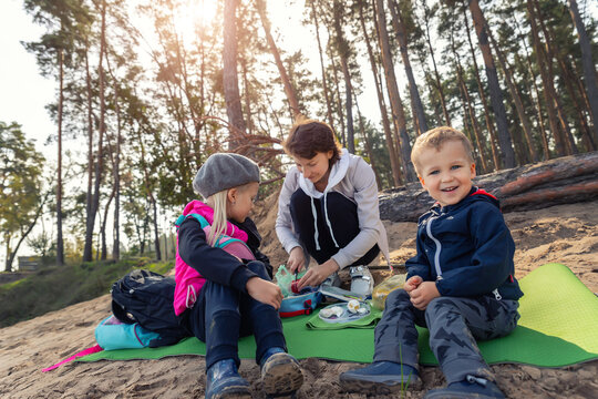 Young adult caucasian beautiful mother enjoy having fun eating snack on picnic with two cute little children in pine forest outdoors on warm autumn day. Family nature outdoor recreation lifestyle
