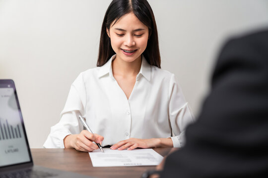 Businesswoman signing financial contract and hand holding pen putting signature after reaching agreement.