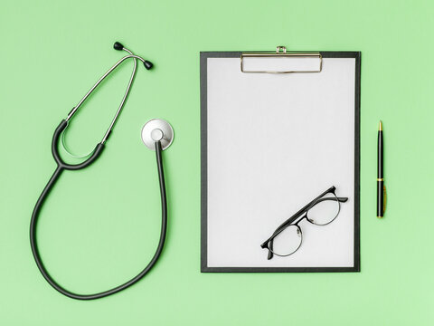 Doctor's desk top view. Stethoscope and notebook on a colored background