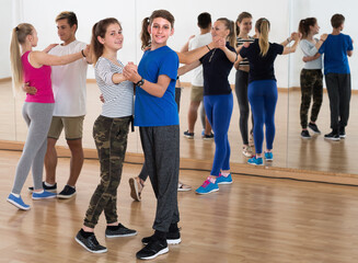 Portrait of teen boys and girls having dancing class in classroom