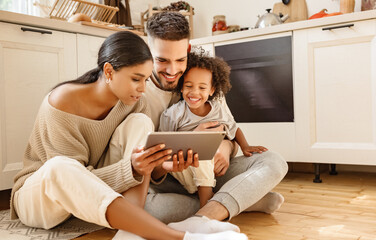 happy multi ethnic family: parents and son using tablet  at home