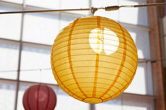 a yellow rice lamp hanging from the ceiling