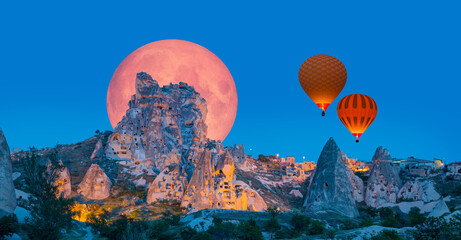 Hot air balloon flying over Uchisar castle with full moon