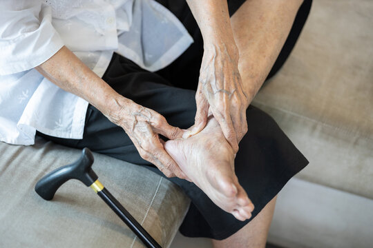Old elderly with foot injuries,heel pain or ankle diseases,asian senior woman suffer from plantar fasciitis,tendon connecting calf muscles to the heel injury,achilles tendinitis after walk exercising