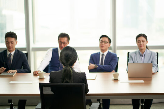 female asian candidate being interviewed by a group of business people