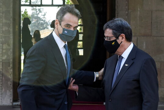 Cyprus' President Nicos Anastasiades welcomes Greece's Prime Minister Kyriakos Mitsotakis before a trilateral summit between Greece, Cyprus and Egypt, at the Presidential Palace in Nicosia