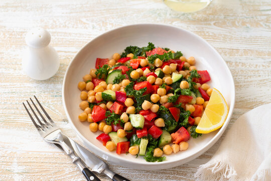 Healthy vegan salad with chickpeas, tomatoes, cucumbers, bell peppers and kale on light wooden background