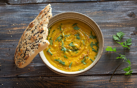 Indian lentil masurdal soup with turmeric, ginger and herbs, top view