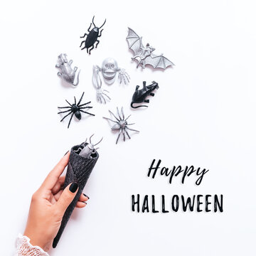 Happy Halloween frame on white with black and silver holiday decor. Silver bats and ghosts flying around, copy space, gothic Halloween holiday flat lay