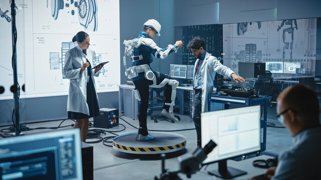 In Robotics Development Laboratory: Engineers and Scientists Work on a Bionics Exoskeleton Prototype with Person Testing it. Designing Wearable Exosuit to Help Disabled People, Warehouse Workers