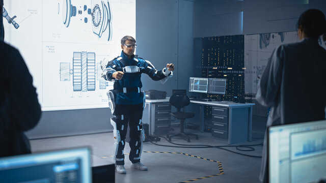 In Development Laboratory: Engineers and Scientists Look at Robotics Exoskeleton Prototype Presentation with Person Testing it, Performing and Standing. Designing Wearable Exosuit to Help People