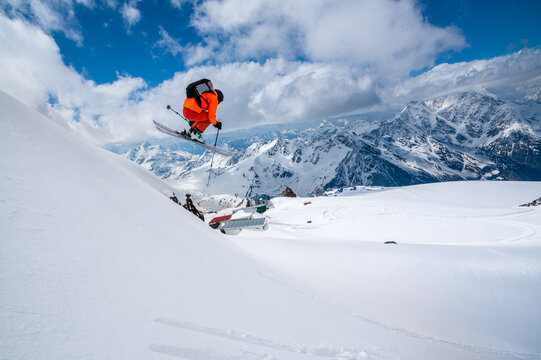 Professional athlete skier freerider in an orange suit with a backpack flies in the air after jumping on the lags on the background of blue snow and mountains